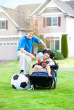 Father playing soccer with disabled son in wheelchair at park Royalty Free Stock Photo