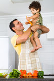 Father playing with son. Happy father playing in modern kitchen with toddler son Stock Photography