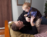 Father playing with son. Young father lying on bed playing with preschool son stock photos