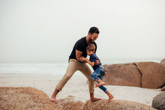 Father playing with son on the beach. Shot of father and son on the beach vacation. Young men playing with little boy at the sea shore. Jumping on the rocks Royalty Free Stock Photos