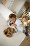 Father playing with son and daughter (6-8) on sofa at home, elevated view (tilt) stock images