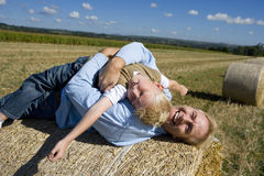 Father playing with son (7-9) on hay bale, smiling, portrait, elevated view Royalty Free Stock Image