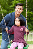Father is playing on swing with her daughter Royalty Free Stock Photo