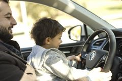 Father playing teaching baby to drive car while waiting inside f Stock Photo