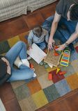 Father playing with toddler while the mother is looking at them. Young father playing with their toddler a wooden game building in the living room while the Stock Image