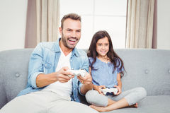 Father playing video game with daughter at home Royalty Free Stock Image