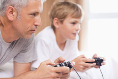 Father playing video games with his son. In a bedroom Stock Images