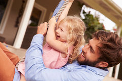 Free Father Playing With Daughter On A Rope Swing In A Garden Stock Image - 59872481