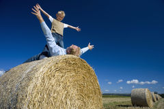 Father Playing With Son (7-9) On Hay Bale, Arms Outstretched, Low Angle View Royalty Free Stock Image