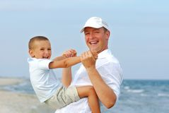 Father playing with young son on the beach. Beautiful adult father playing with young son on beach Stock Photography