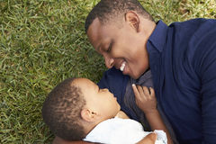 Father Playing With Young Son On Grass In Summer Park Stock Photos