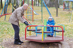 Father plays with baby son of 1 year in autumn on playground Stock Images