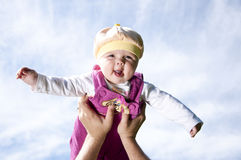 Father plays with the child. Father playing with baby, raised it high above them Stock Image