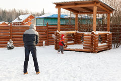 Father plays with child snowballs in backyard Stock Photo
