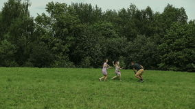 Father plays with children in field stock footage