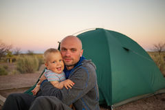 A father plays with his baby son at the tent in campground Royalty Free Stock Photo