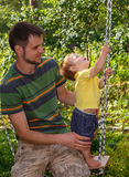 Father plays with his little son on the swing Stock Images