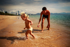 father plays with little daughter in shallow water on beach Stock Photos