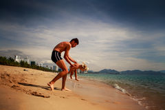 Father plays with little daughter in shallow water on beach Royalty Free Stock Photography