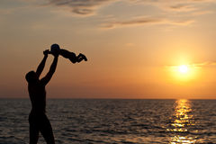 Father plays with son against a sunset Royalty Free Stock Photography