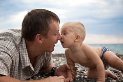 Father plays with son on a beach. (against sea stock photo