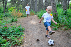 The father plays with the son soccer in the wood. The father, the son and a football ball stock images