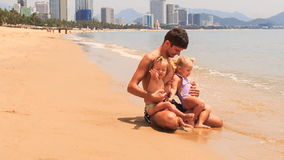 Father plays two little girls sitting on edge of sea on beach. Father plays with two little blonde girls with hairtails in swimsuits sitting on edge of sea on stock video