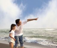 Father pointing and little girl looking. It on the beach Stock Photography