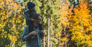 Father pointing out something to son in the autumn forest while holding him in arms royalty free stock photo
