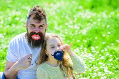 Father posing with lips and child posing with beard photo booth attribute. Gender roles concept. Dad and daughter sits. On grassplot, grass on background royalty free stock photo