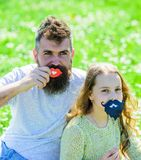 Father posing with lips and child posing with beard photo booth attribute. Gender roles concept. Family spend leisure. Outdoors. Dad and daughter sits on royalty free stock image