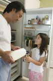 Father Pouring Milk For Daughter by fridge in kitchen Stock Images