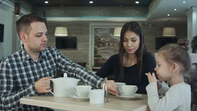 Father pouring tea to his wife and daughter in restaurant. Mother petting daughter on the head. stock video