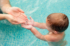 Father pouring water in hands of his son Royalty Free Stock Photo