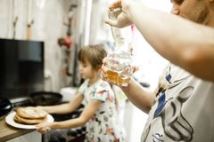 Father pours honey in the bowl and his little daughter takes a plate with pancakes in the kitchen royalty free stock photos