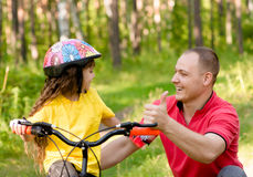 Father praises his daughter, who learned to ride a bike Stock Photos