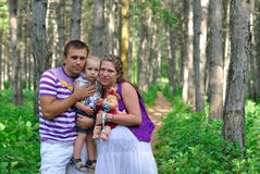 The father, pregnant mother and the child. Family with pregnant mother on a footpath in the pine wood Royalty Free Stock Photo