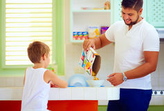 Father preparing cornflakes for son in the morning, breakfast at home Royalty Free Stock Photo