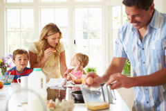 Father Preparing Family Breakfast In Kitchen. Happy Father Preparing Family Breakfast In Kitchen Cracking Eggs Stock Photo