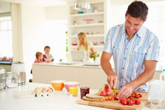 Father Preparing Family Breakfast In Kitchen. Using Knife And Chopping Board royalty free stock images