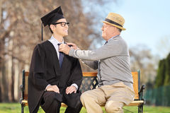 Father preparing his son for graduation in park. Father preparing his son for graduation seated on wooden bench in park royalty free stock photo