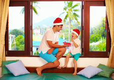 Father presenting son a tasty candies on christmas, while sitting on windowsill in tropics Stock Photo