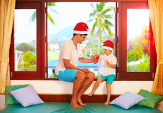 Father presenting son a tasty candies on christmas, while sitting on windowsill in tropics Royalty Free Stock Image