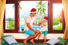 Father presenting son a tasty candies on christmas, while sitting on windowsill in tropics Stock Image