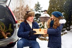 Father presents daughter a gift box on snowy winter day outdoors. Christmas tree in large trunk of family car. Girl. Father presents daughter a gift box on snowy royalty free stock image