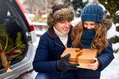 Father presents daughter a gift box on snowy winter day outdoors. Christmas tree in large trunk of family car. Girl. Father presents daughter a gift box on snowy royalty free stock photo