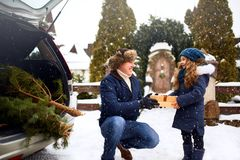 Father presents daughter a gift box on snowy winter day outdoors. Christmas tree in large trunk of family car. Girl. Father presents daughter a gift box on snowy royalty free stock photos