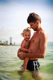 Father presses to breast little daughter in sea water Royalty Free Stock Photography
