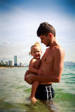 Father presses to breast little daughter in sea water Royalty Free Stock Photos