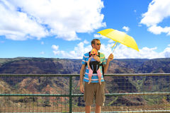 Father protecting his lovely baby with an umbrella. Waimea Canyo Royalty Free Stock Photo
